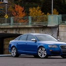 Awesome blue Audi S6 parked in parking lot near bridge