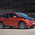 Gorgeous look of orange BMW i3 running on a road for testing